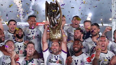 The Storm celebrate with the premiership trophy at ANZ Stadium on Sunday.