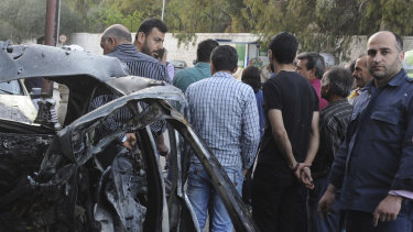 This photo released by the Syrian official news agency SANA, shows Syrians gathered next to a bunt car hit by a shelling by members of the Army of Islam rebel group at Rabwa neighborhood in Damascus, Syria, on Friday.
