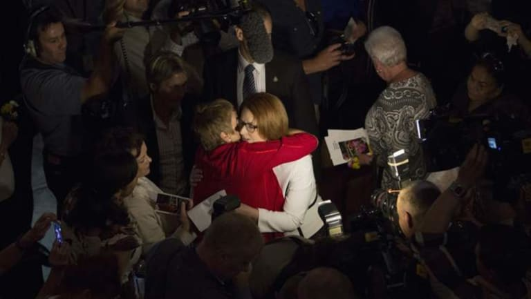 Julia Gillard embraces members of the audience after the National Apology for Forced Adoptions.