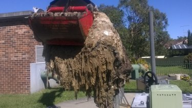 Sydney Water workers at the Shellharbour sewage pumping station cleaning out a blockage of wet wipes also known as a fatberg.