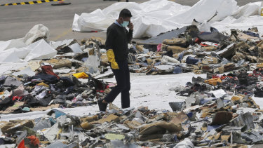 An investigator walks amid debris of Lion Air Flight 610 retrieved from the waters off Tanjung Priok in Jakarta.