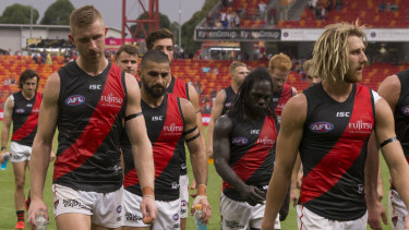 Dyson Heppell (right) leads the defeated Bombers from the field