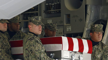 A US Navy  team on Saturday moves a transfer case containing the remains of a serviceman killed  in last week's suicide bomb attack in Manbij, Syria.