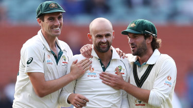 Nathan Lyon celebrates with Pat Cummins and Joe Burns after taking the wicket of Shaheen Shah Afridi.
