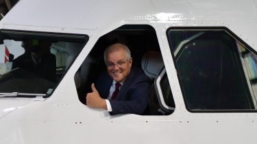 Prime Minister Scott Morrison leaning out of a Qantas plane on Thursday ahead of announcing the $1.2 billion industry package.