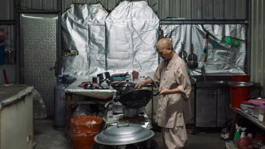 A nun cooks inside a shed that houses Buddhist nuns evicted from their temple in Ershu.