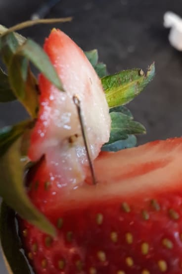 A photo of a contaminated strawberry posted to social media.