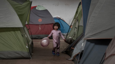 A girl holds a balloon as she walks among tents inside an empty warehouse used as a shelter set up for migrants in downtown Tijuana, Mexico.