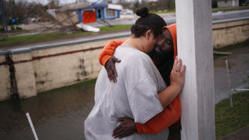 Residents embrace in front of an apartment building after Hurricane Michael hit in Panama City in Florida on Wednesday.