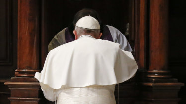 Pope Francis kneels in confession during a penitential liturgy in St. Peter's Basilica at the Vatican.