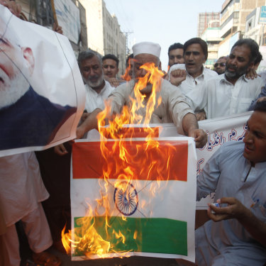 Pakistanis burn an Indian flag in protest over the Kashmir decree.