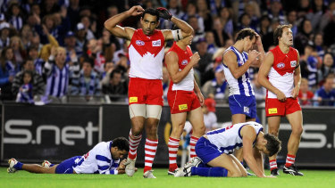 Swans and Kangaroos players exhausted as the final siren signals a draw.