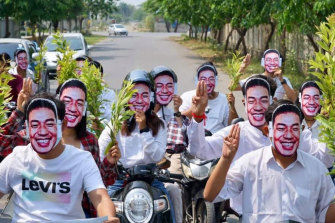 """Supporters of the Myanmar alternative """"national unit government"""" pose with masks of its spokesman, Dr Sasa."""