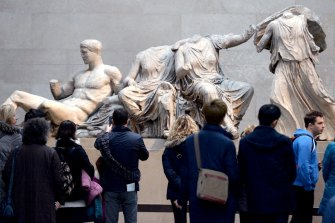 Visitors look at The Parthenon Marbles, also known as the Elgin Marbles in the British Museum.