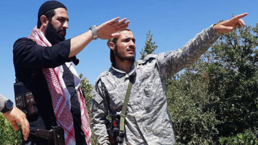 This undated file photo released by the militant group Levant Liberation Committee on  August  21, shows Abu Mohammed al-Golani of the militant Levant Liberation Committee and the leader of Syria's al-Qaida affiliate, left, talking with a fighter, in the countryside of Latakia, Syria.