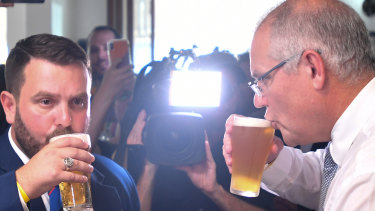 Scott Morrison sips his beer alongside the Liberal candidate for Herbert, Phillip Thompson, on Anzac Day.