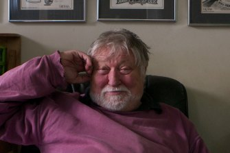 Ron Cobb, at home in Rozelle, Sydney, in 2012. Some of his 1960s cartoons are on the wall behind him.