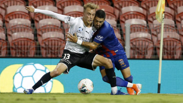 Dimi Petratos of the Jets contests the ball with Nathaniel Atkinson of Melbourne City.