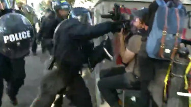Footage shows Channel Seven cameraman Tim Myers being punched by a police officer while covering protests outside the White House.