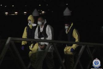 The men under police guard after their arrest.
