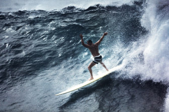 Noll surfing Waimea in his black striped boardshorts.