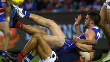 Flat out: Bailey Williams gets boot to ball after being taken down by Demon Neville Jetta.