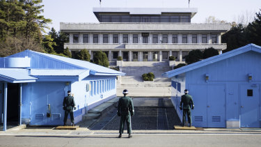 South Korean soldiers guard the border between South and North marked by a short concrete wall in the DMZ.