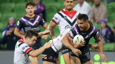Head knock: Roosters five-eighth Luke Keary reels out of a tackle after tackling Storm fullback Jahrome Hughes.