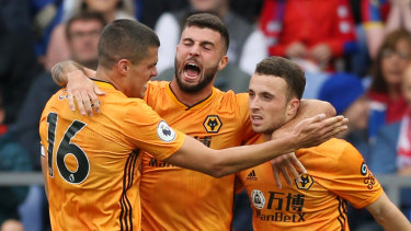 Patrick Cutrone of Wolverhampton Wanderers celebrates with teammates Diogo Jota and Conor Coady after scoring the equaliser against Palace.