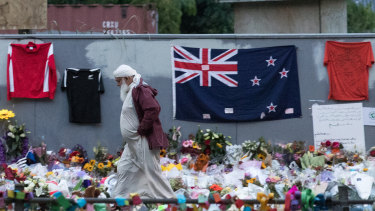 A Muslim man walks past a makeshift memorial on the walls surrounding the Al Noor Mosque following the Christchurch attack.
