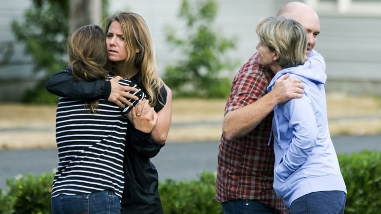 Friends of Richard Russell  hug in disbelief on Saturday.
