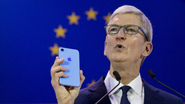 Apple boss Tim Cook holds up an iPhone as he speaks during a data privacy conference in Brussels.
