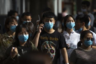 People wearing face masks to protect against the spread of the new coronavirus walk along a pedestrian shopping street in Beijing, Saturday, May 16, 2020.