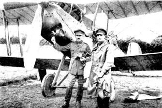 Captain Youdale is seen pointing to a hole in his biplane caused by a shell. On a previous flight he returned with 30 bullet holes.