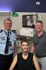 Queensland Police Constable Peter McAulay in hospital with his father Mike and Police Commissioner Ian Stewart.