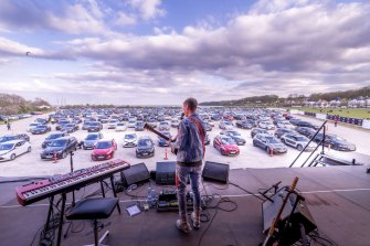 Danish musician Mads Langer performs to an audience in socially distanced cars.