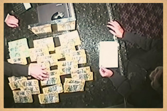 Roy Moo, right, on surveillance footage piling cash onto the counter at Crown casino in Melbourne. This recording was presented in court.