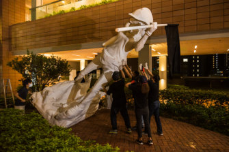 University students move a statue of Lady Liberty last month.