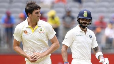 Fair play: Indian captain shares a smile with Australian paceman Pat Cummins on day three.