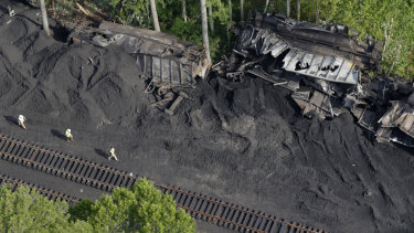 Workers are seen around the site after 36 railroad cars containing 3600 tonnes of coal derailed in the Great Dismal Swamp  in Virginia.