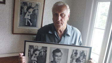 George Mendonsa poses for a photo in 2009 with a copy of the iconic 1945 photo.