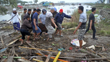 Residents carry the body of a tsunami victim in Palu, Central Sulawesi.