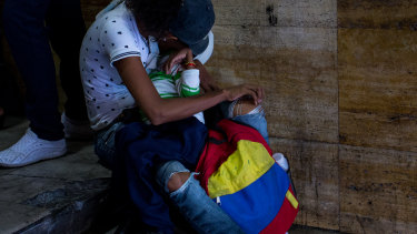 A woman cradles her chronically sick child at a demonstration protesting health cuts outside  Venezuela's Health Ministry last week.