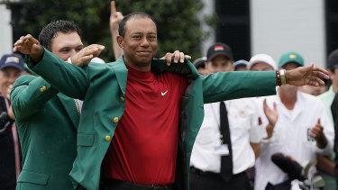 Tiger Woods dons the famous green jacket after his long-awaited victory at the US Masters on Monday.