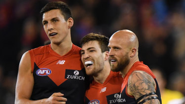 In with a shout: Jack Viney, centre, and Demons teammates.