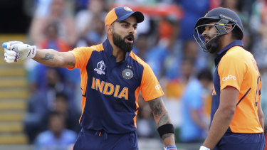 """Unimpressed: India captain Virat Kohli speaks with Rohit Sharma after hitting a four against England. He called the short boundary at Edgbaston that played into the hands of the home side """"bizarre""""."""