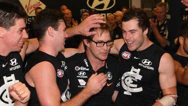 Carlton players celebrate with caretaker coach David Teague.