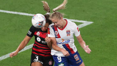 Jets striker Tara Andrews wins a header against the Wanderers.