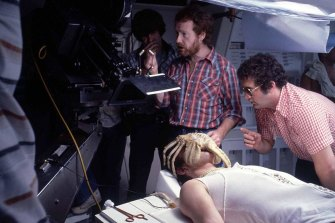 "Ridley Scott (with beard) directs a scene featuring the creature in ""facehugger"" form."