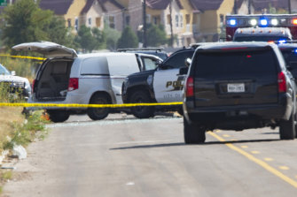 Odessa and Midland police and sheriff's deputies surround a white van in Odessa, Texas, following the shooting.